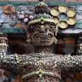 A demon supporting the stupa decorated with pieces of Chinese porcelain at Wat Arun, the Temple of Dawn